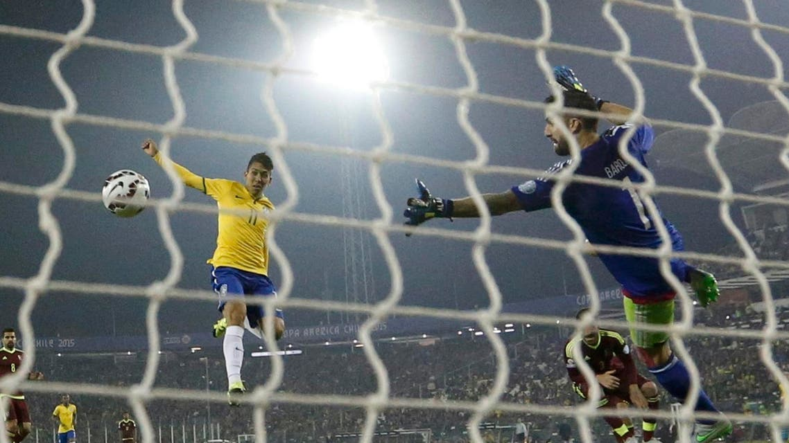 Brazil's Firmino scores past Venezuela's goalie Baroja during their first round Copa America 2015 soccer match at Estadio Monumental David Arellano in Santiago. (Reuters)