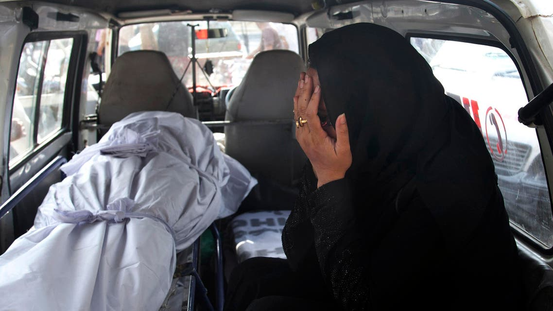 A Pakistani woman mourns as she sits beside the lifeless body of her relative who died from a heatstroke, inside an ambulance at a morgue of a charity group, in Karachi, Pakistan, Monday, June 22, 2015. (AP)