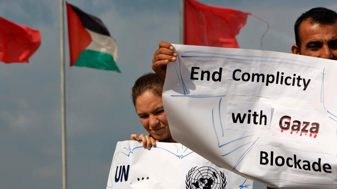 Palestinian and foreign activists hold placards in front of Palestinian and Turkish flags during a rally to show their support for two boats carrying 27 civilians from various countries attempting to reach the Gaza Strip, in the sea port of Gaza City Friday, Nov. 4, 2011. AP