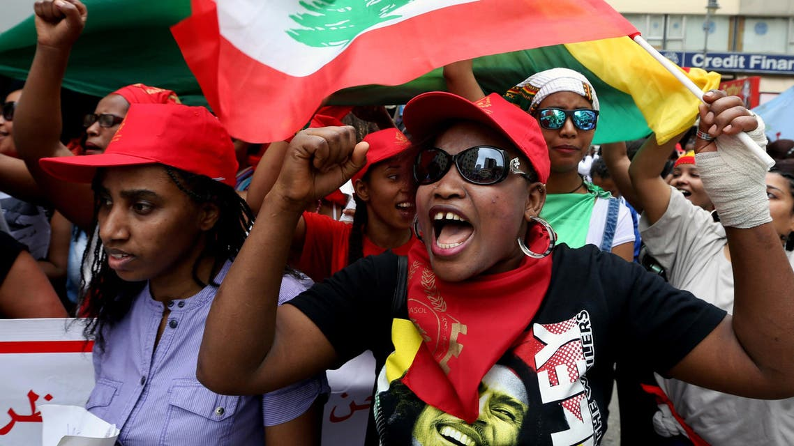 Migrant domestic workers chant slogans as they carry Lebanese flags during a march demanding basic labor rights as Lebanese workers in Beirut, Lebanon, Sunday, May 3, 2015.AP