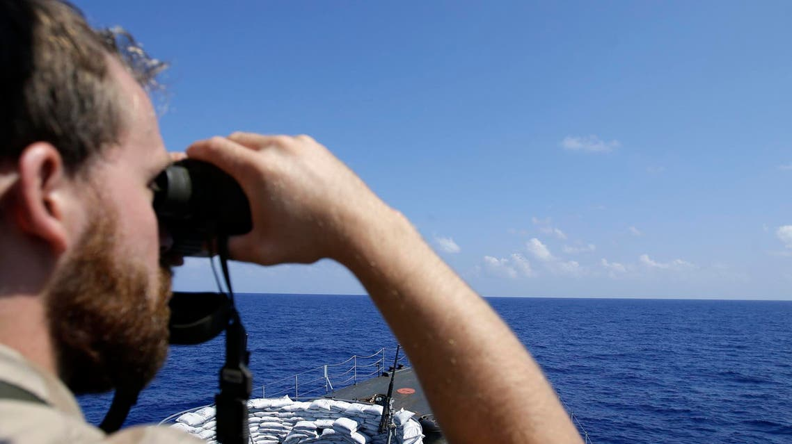 Gregori Nills, a crew member of the command bridge, looks through binocular aboard of the Belgian Navy Vessel Godetia during a migrants search and rescue mission in the mediterranean sea off the Sicilian coasts, Italy, Saturday, June 20, 2015. AP