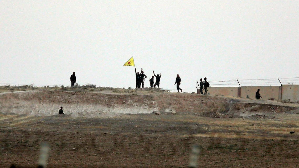In this photo taken from the Turkish side of the border between Turkey and Syria, in Akcakale, southeastern Turkey, Kurdish fighters with the Kurdish People's Protection Units, or YPG