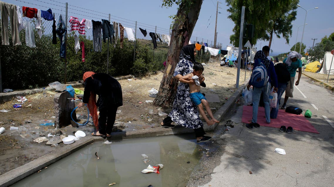 In this photo taken on Tuesday, June 16, 2015 a woman holds up a child to pass dirty water at a migrant and refugee camp in Mytilene, on the northeastern Greek island of Lesbos (AP)