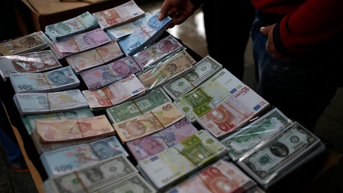 A man holds a pack of Turkish Liras, featuring images of Turkish Republic founder Mustafa Kemal Ataturk, among other foreign currency, at a currency exchange office in Istanbul, Turkey, Monday, June 8, 2015. (AP)