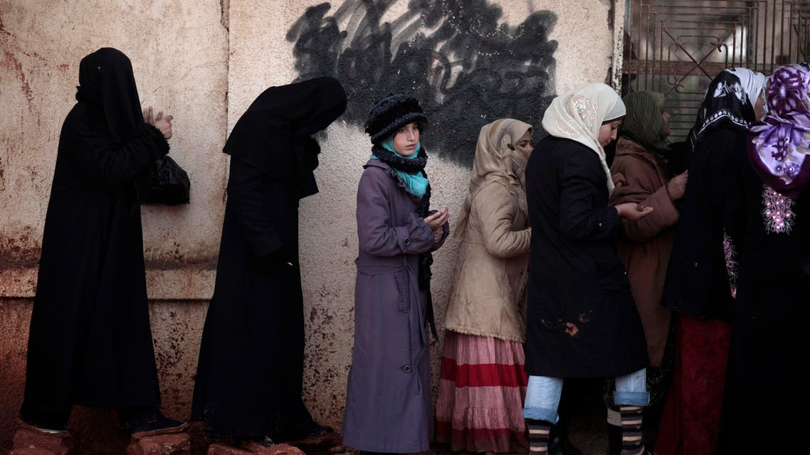 In this Wednesday, Dec. 12, 2012, file photo, Syrian women wait outside a bakery shop to buy bread in Maaret Misreen, near Idlib, Syria. (AP)