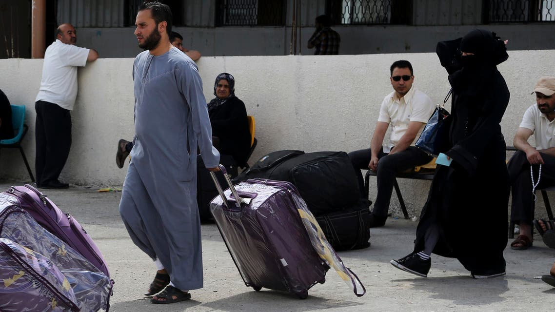 A Palestinian couple push their luggage heading to the bus as others wait to cross to the Egyptian side of the Rafah border crossing, in the southern Gaza Strip, Tuesday, June 23, 2015.  (AP)