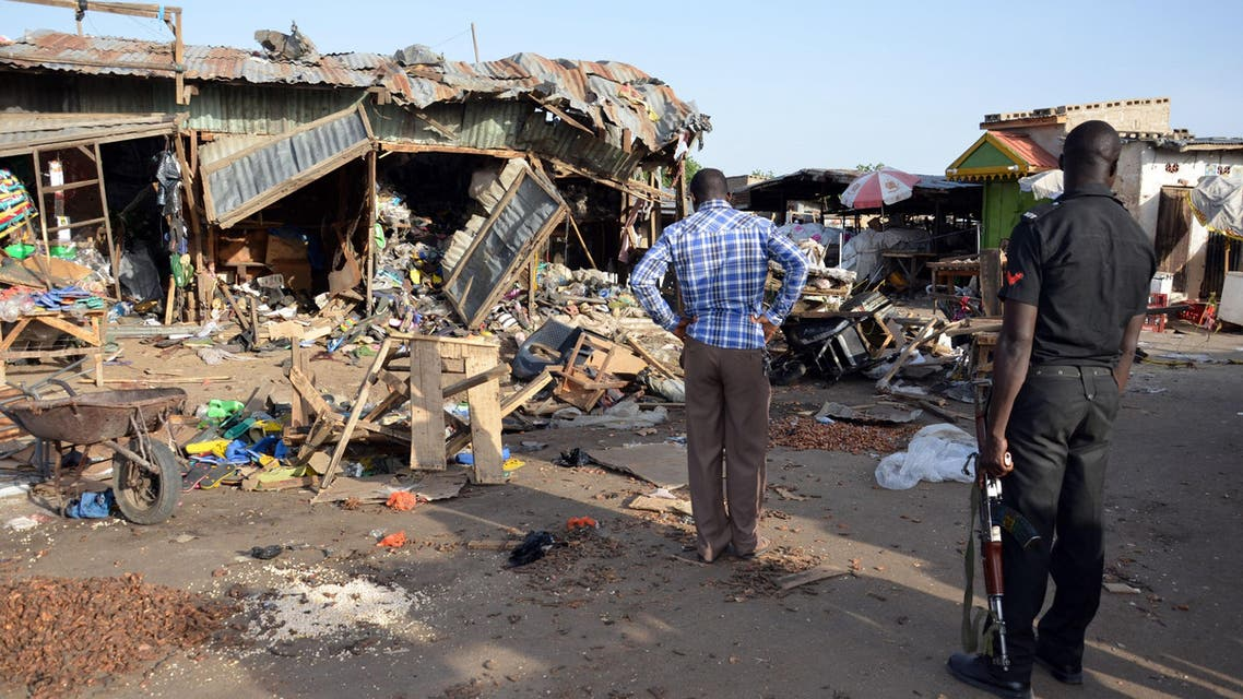 A police officer stands at the scene of a bombing after at least 20 people were killed when a young female suicide bomber detonated her explosives at a bus station in Maiduguri, northeast Nigeria, on June 22, 2015 AFP