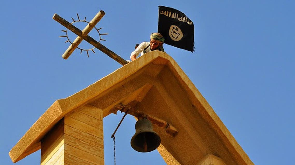 In this photo released on March 7, 2015 by a militant website, which has been verified and is consistent with other AP reporting, a member of the Islamic State group holds the IS flag as he dismantles a cross on the top of a church in Mosul, Iraq.