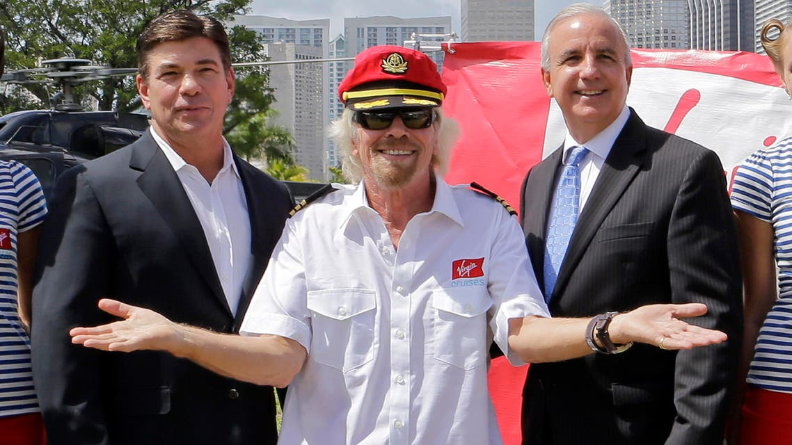 Richard Branson, founder of the Virgin Group, center, Virgin Cruises CEO Tom McAlpin, left, and Miami-Dade County Mayor Carlos Gimenez, right, pose for photos, Tuesday, June 23, 2015, at Perez Art Museum in Miami. Branson and McAlpin announced that Virgin Cruises will set sail from PortMiami in 2020.
