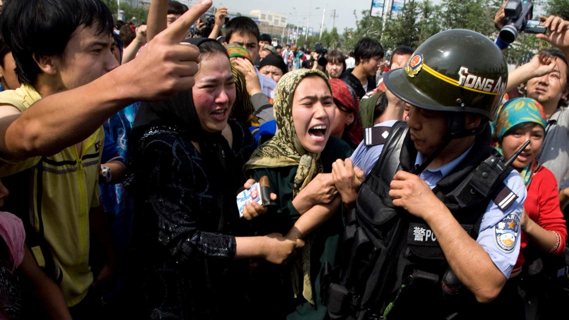Uighur women grab a police officer as they protest in front of journalists visiting the area in Urumqi, China on July 7, 2009. (File Photo: AP)
