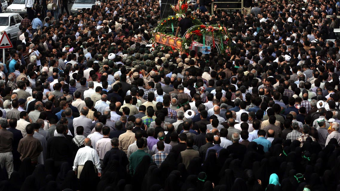 Iranian mourners touch the coffins of Mohammad Hamidi, Hasan Ghafari and Ali Amrai, members of the Islamic Republic's Revolutionary Guards reportedly killed in Syria, during their funeral in Tehran on June 25, 2015. (AFP)
