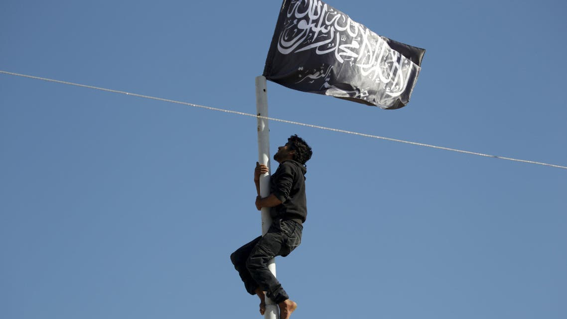 A member of al Qaeda's Nusra Front climbs a pole where a Nusra flag was raised at a central square in the northwestern city of Ariha, after a coalition of insurgent groups seized the area in Idlib province May 29, 2015. Reuters