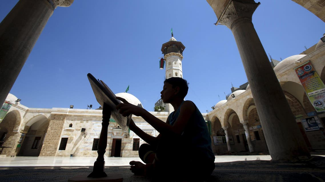 A Palestinian boy reads the Koran during the holy month of Ramadan at Sayed Hashim Mosque in Gaza City June 23, 2015. Reuters