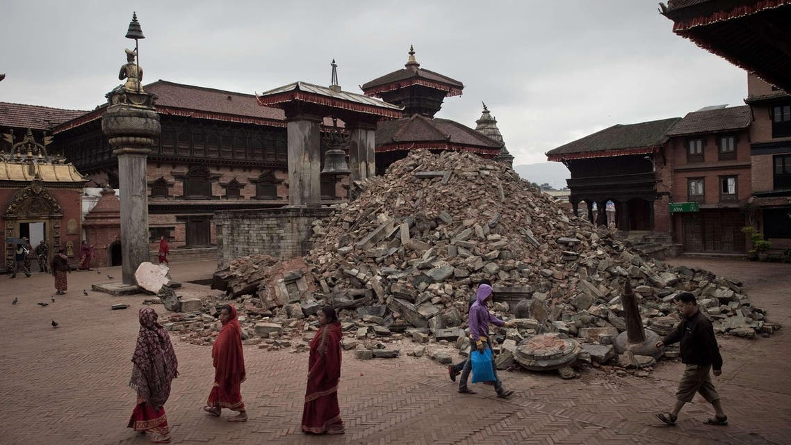 In this photograph taken on April 30, 2015, pedestrians walk past damaged temples at the UNESCO world heritage site of Bhaktapur on the outskirts of the Nepalese capital Kathmandu, following a 7.8 magnitude earthquake which struck the Himalayan nation on April 25. AFP