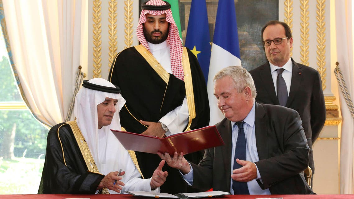 Eurocopter Senior Vice President for Sales and Customer Relations Olivier Lambert (R) exchanges documents with Saudi Foreign Minister Adel al-Jubeir, after signing an agreement for the sale of 23 helicopters to Saudi Arabia, in front of French President Francois Hollande (Top R) and Saudi Arabia's Deputy Crown Prince Mohammed bin Salman at the Elysee Palace in Paris, France, June 24, 2015. Reuters