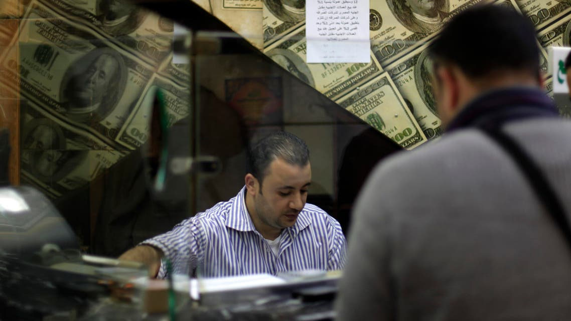 An Egyptian man changes U.S. dollars to Egyptian pounds at a currency exchange office in downtown Cairo, Egypt, Wednesday, Jan. 2, 2013. (AP)
