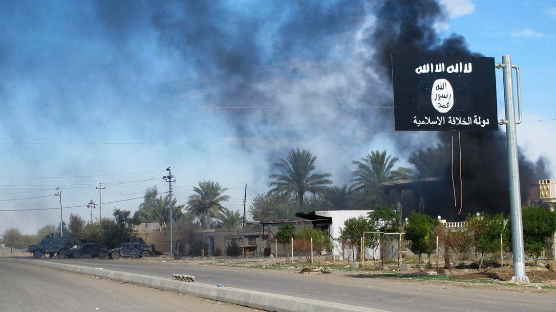 Smoke raises behind an Islamic State flag after Iraqi security forces and Shiite fighters took control of Saadiya in Diyala province from Islamist State militants, November 24, 2014.