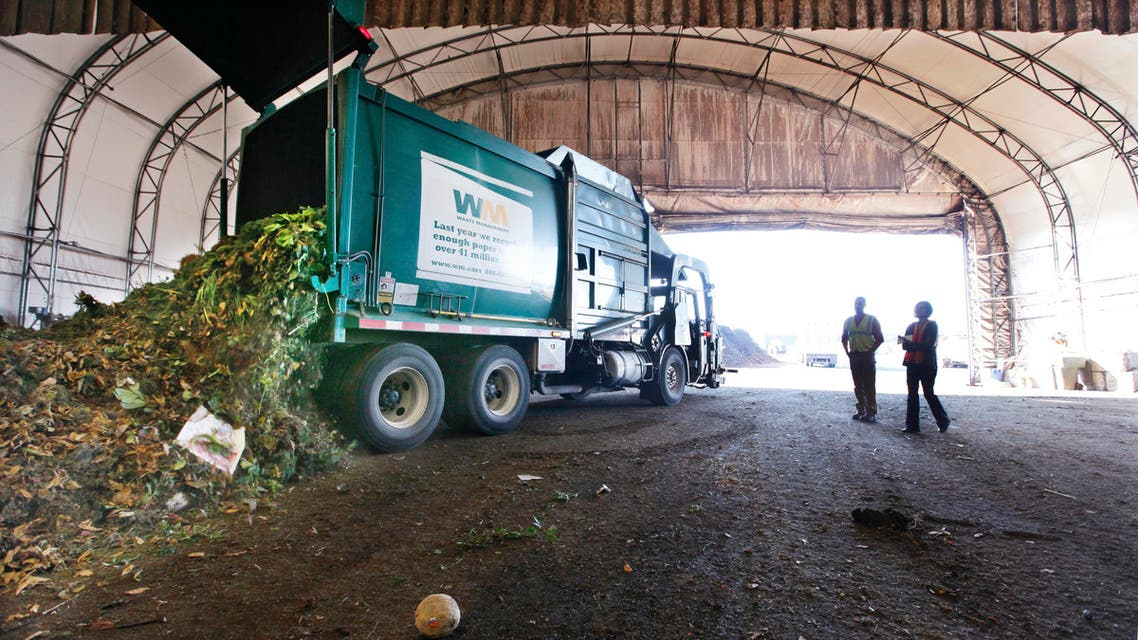 visitors watch as a truck dumps compost materials inside a receiving area at the Cedar Grove processing facility in Everett, Wash. AP