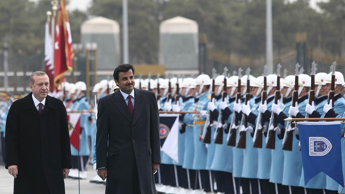Turkish President Recep Tayyip Erdogan, left, and Qatar's Emir Sheikh Tamim bin Hamad Al-Thani inspect a military honour guard at the new presidential palace in Ankara, Turkey, Friday, Dec. 19, 2014.