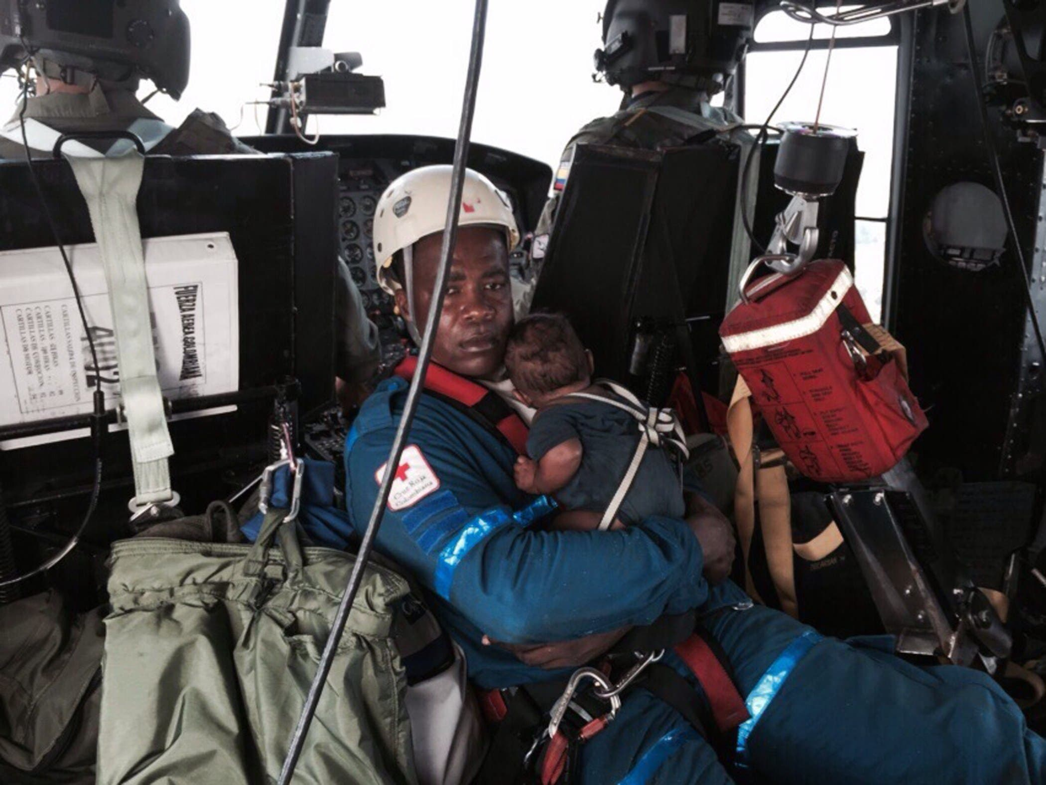 A Red Cross member holding baby Yudier Moreno as he and his mother are transported on a helicopter to a hospital in Quibdo. (AFP)