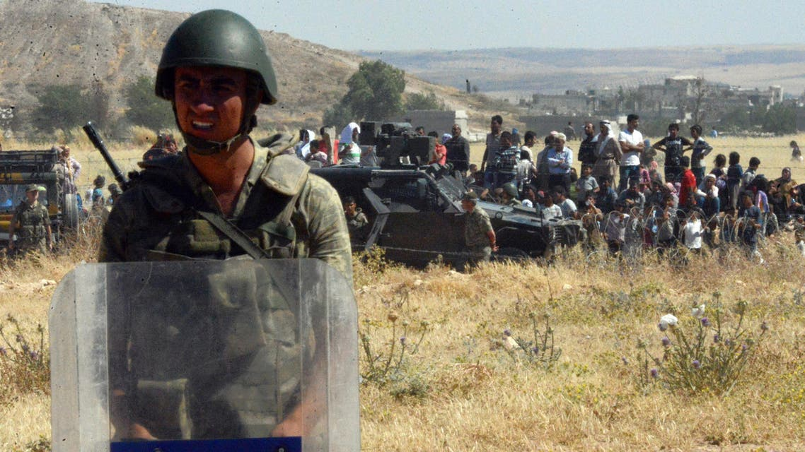 Turkish soldiers stand as people from the Syrian town of Ayn al-Arab or Kobani wait to cross into Turkey following the attacks by IS militants as seen from the Turkish side of the border in Suruc, Turkey, Thursday, June 25, 2015. AP