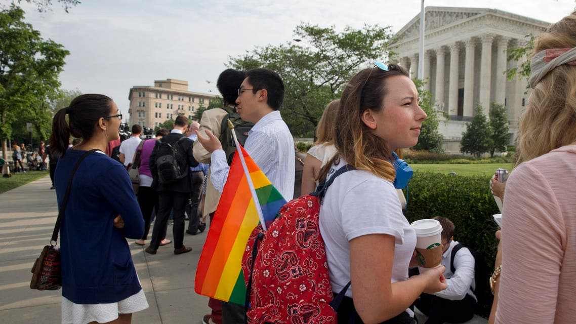 Roxy Moran, 19, an intern on Capitol Hill who is from San Francisco, stands in line with a rainbow flag hoping to get into the Supreme Court in Washington, Friday June 26, 2015. (AP)
