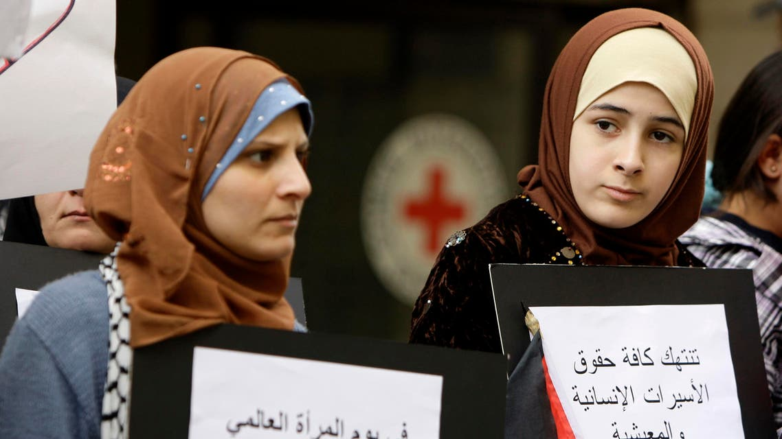 Palestinian women carry banners as they mark International Women's Day in front of the Red Cross offices in Hamra Street, Beirut, Lebanon. (File: AP)