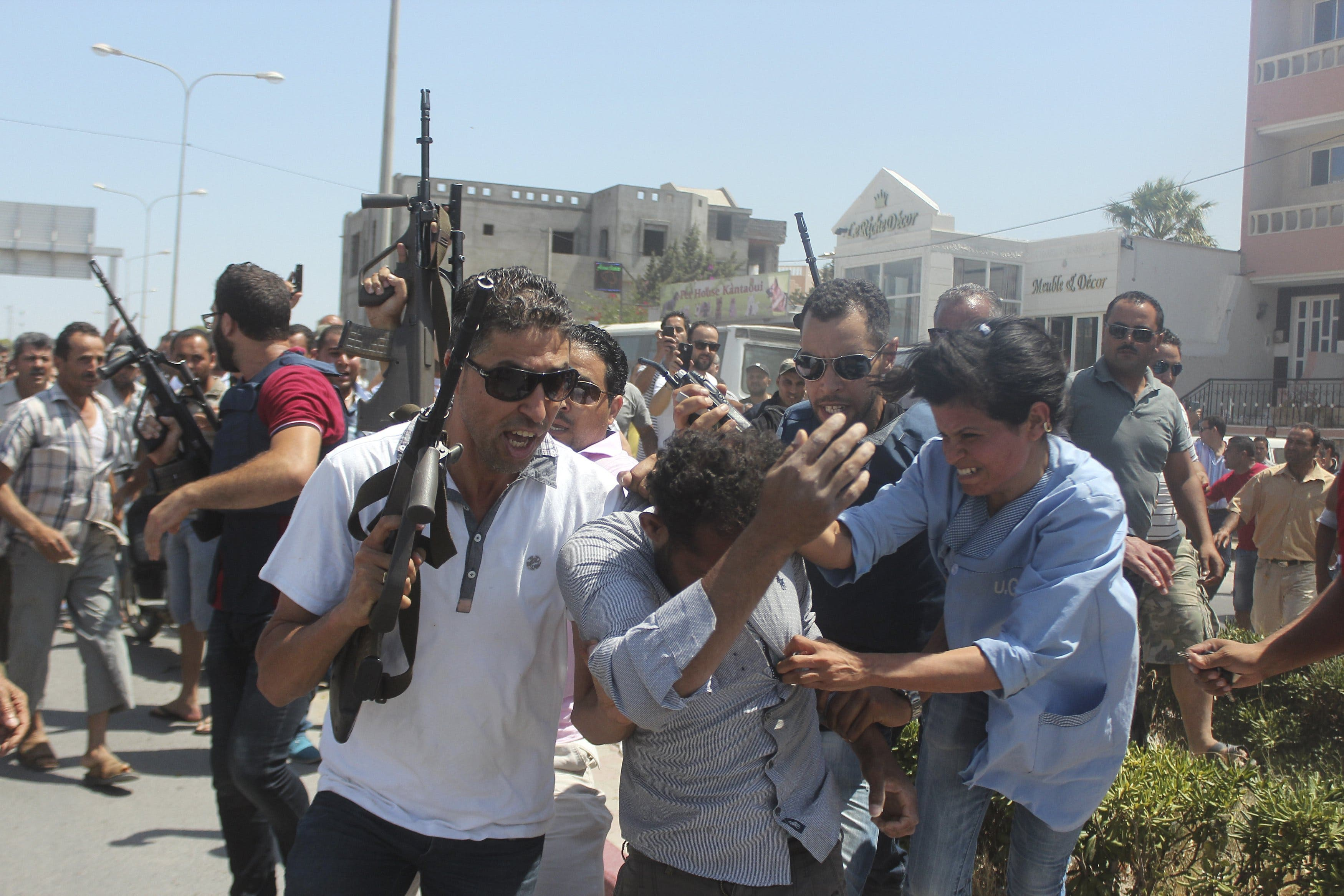 Police officers control the crowd (rear) while surrounding a man (front C) suspected to be involved in opening fire on a beachside hotel in Sousse, Tunisia, as a woman reacts(R), June 26, 2015. Reuters