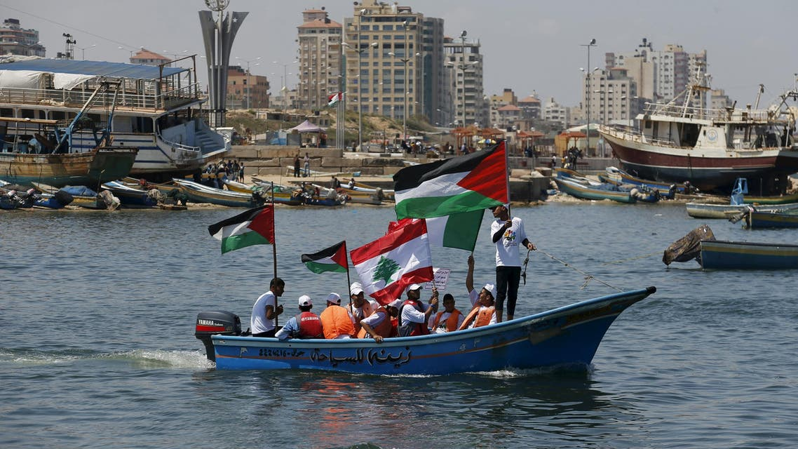 Palestinians hold flags as they ride a boat during a rally marking the 5th anniversary of the Mavi Marmara Gaza flotilla incident
