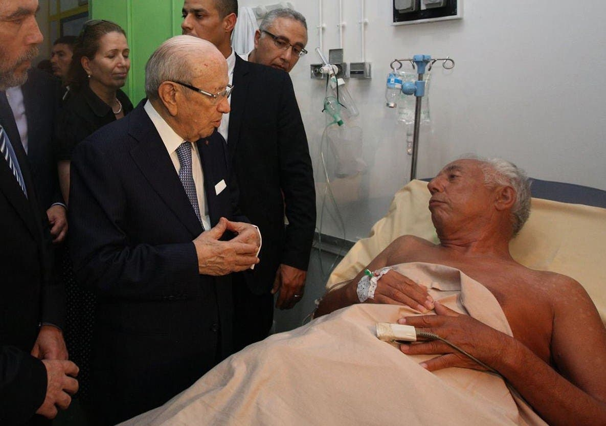 A handout picture release by the Tunisian Presidency on its Facebook page on June 26, 2015, shows Tunisia's President Beji Caid Essebsi (C) visiting a survivor of the mass shooting in the resort town of Sousse, a popular tourist destination 140 kilometres (90 miles) south of the Tunisian capital, at the Sahloul hospital in Sousse. AFP