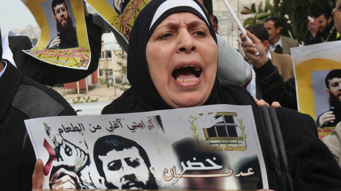 A Palestinian woman holds a poster with the image of Khader Adnan, 33, a senior member of Islamic Jihad jailed in Israel who has been on hunger strike for 54 days. (AP)