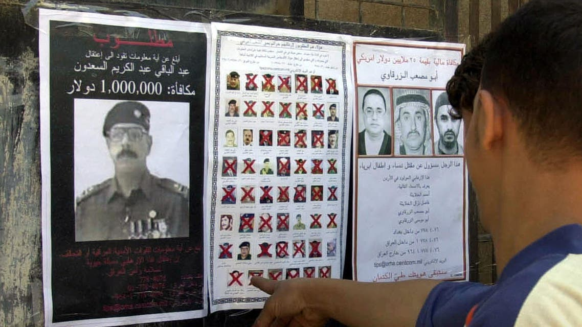 An Iraqi man looks at wanted posters distributed by U.S. forces in Ramadi, Iraq, Monday, March 21, 2005. (AP)
