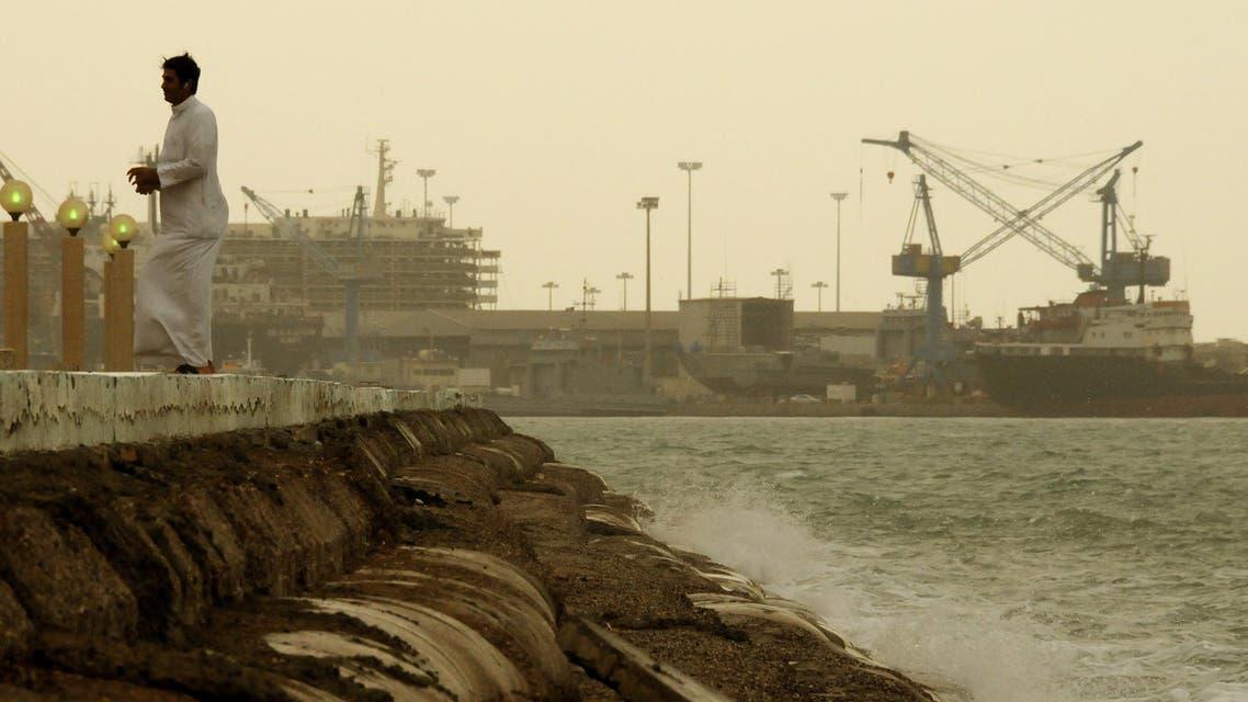 A man walks by the coast near Shuwaikh Port, during a sand storm in Kuwait City. (File: AP)