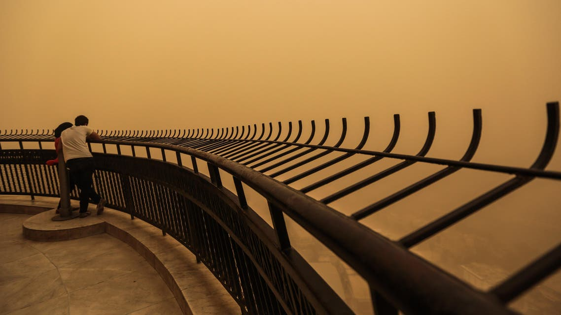 A couple observe a sandstorm that shrouds the capital city from an observation deck of the Cairo Tower in Zamalek, Cairo, Egypt, Saturday, June 27, 2015. (AP)