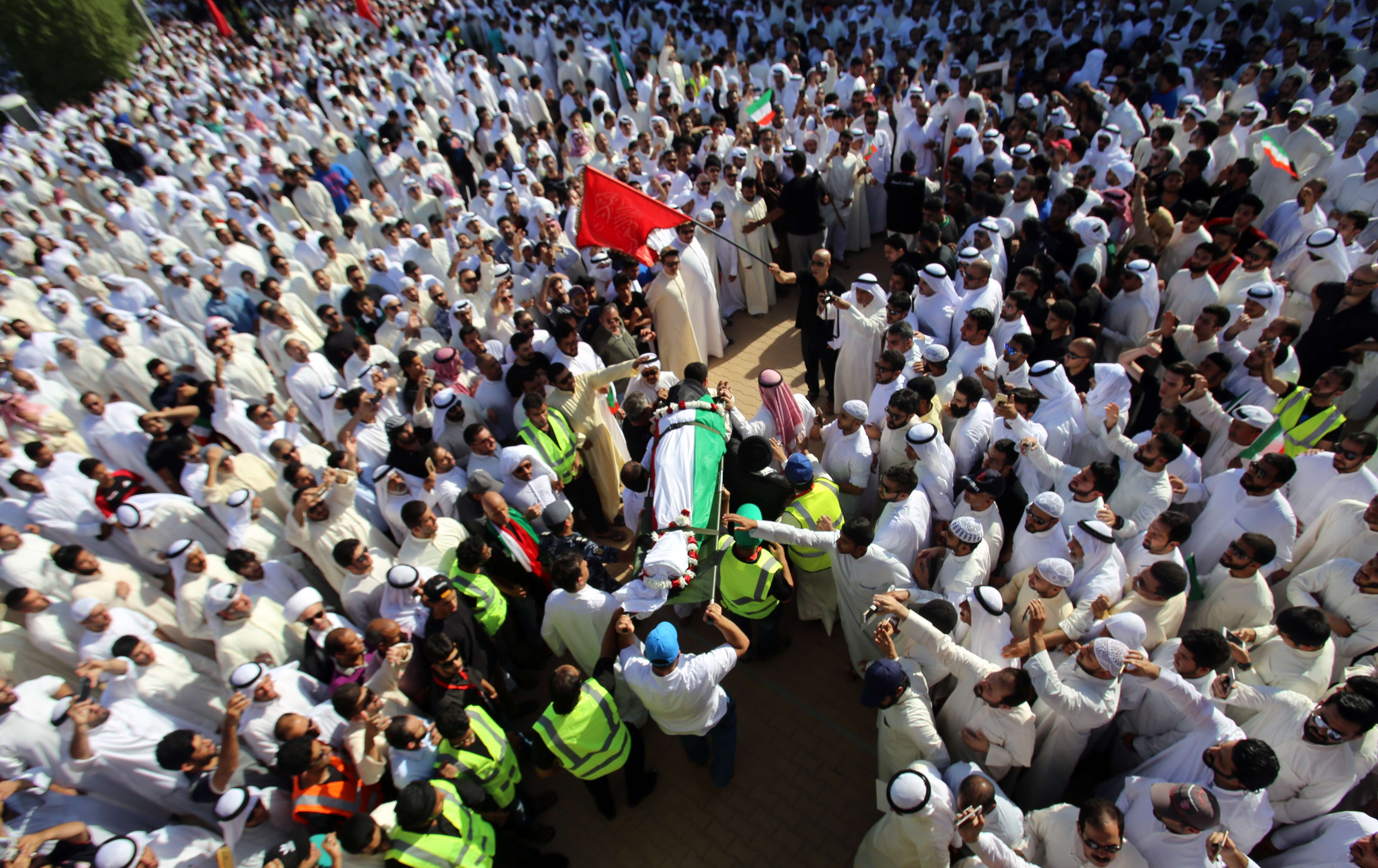 Mourners carry the body of one of the victims of the Al-Imam Al-Sadeq mosque bombing, during a mass funeral at Jaafari cemetery in Kuwait City on June 27, 2015. afp