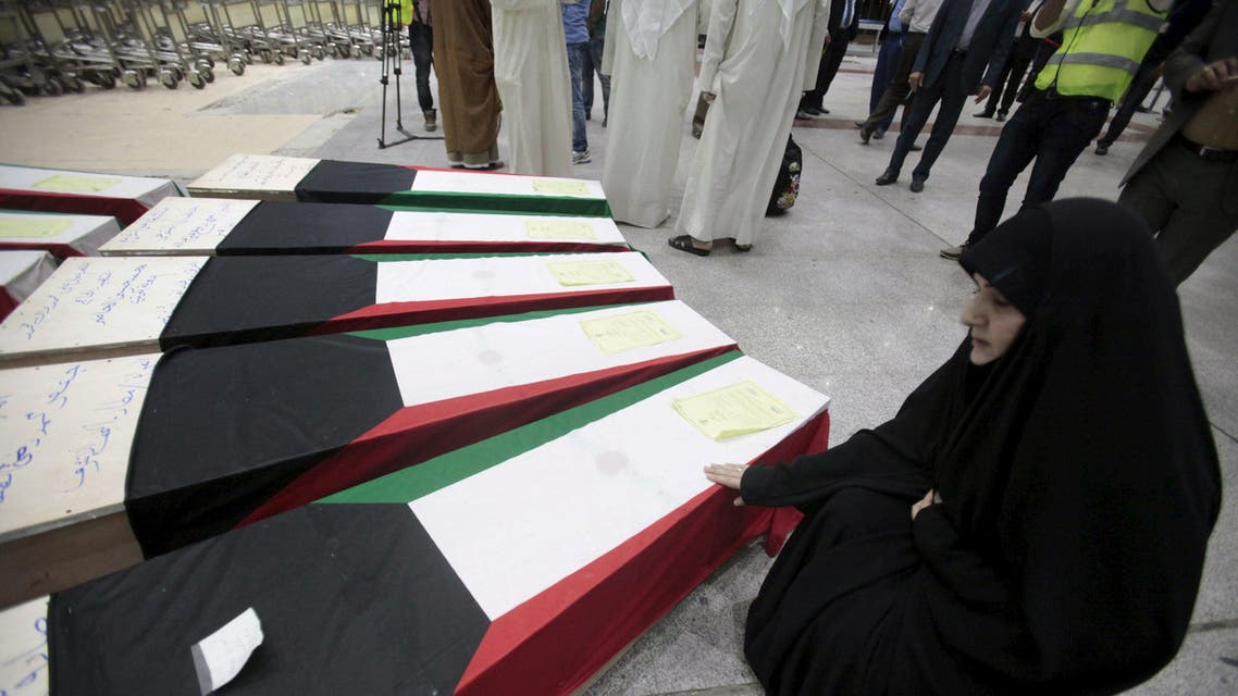 A woman grieves next to coffins of victims of Friday's bombing at the Imam Sadeq mosque in Kuwait City, at the international airport in Najaf. (Reuters)