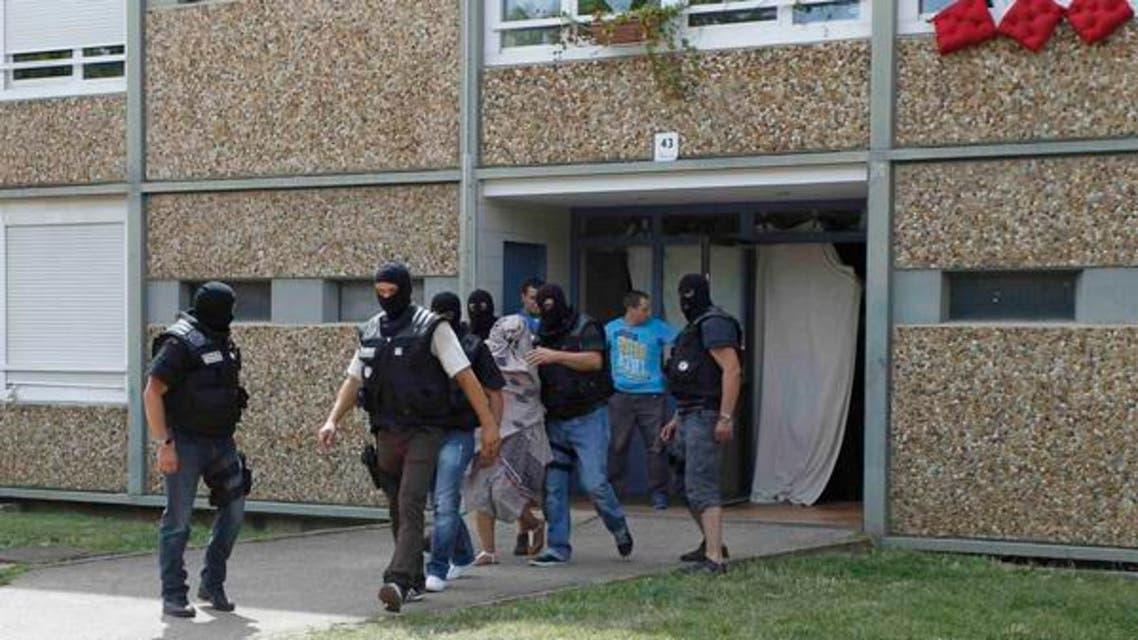 مشتبہ فرانسیسی شخص کی بیوی کو سیکیورٹی اہلکار حراست میں لے رہے ہیں۔