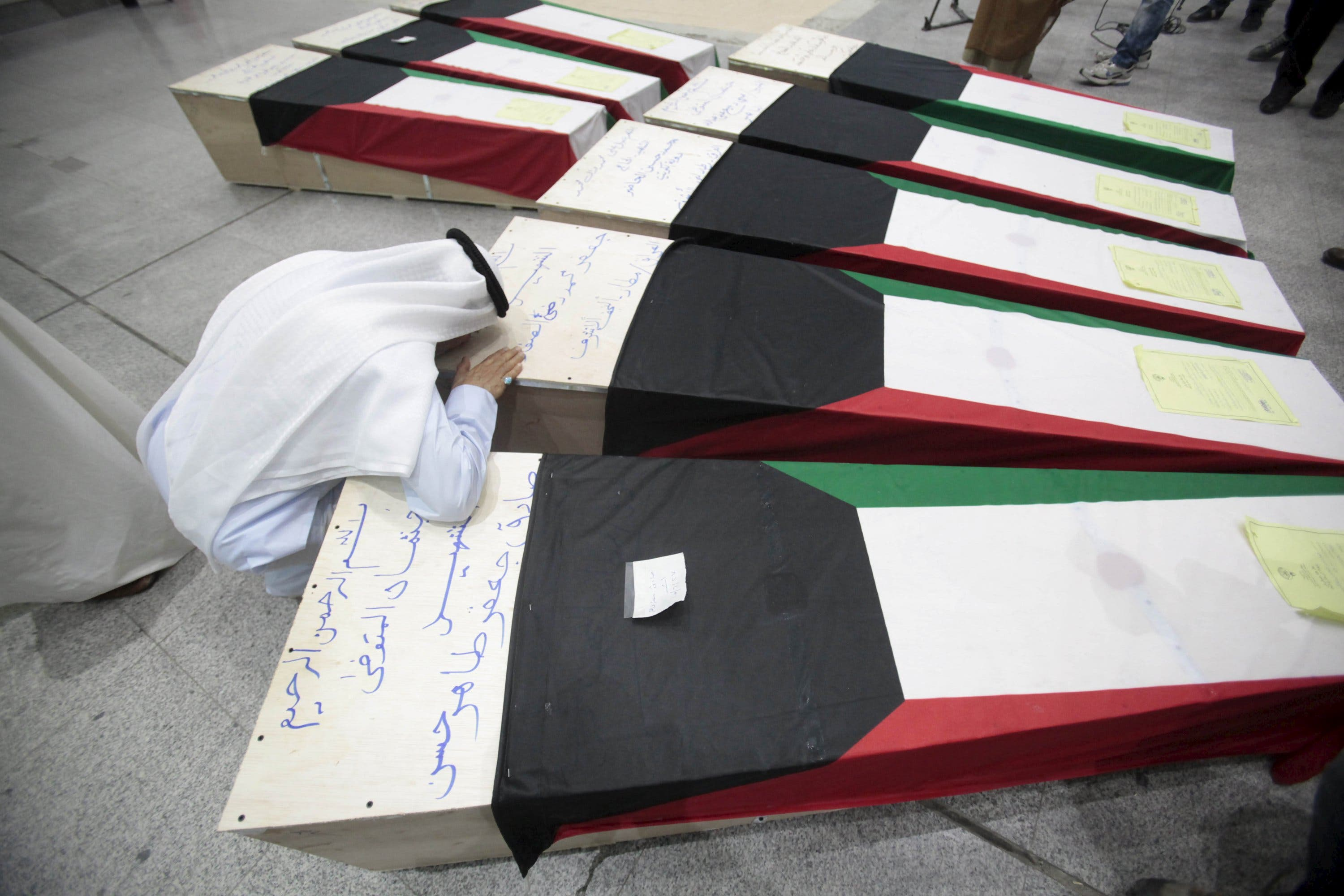 A man reacts next to coffins of victims of Friday's bombing at the Imam Sadeq mosque in Kuwait City, at the international airport in Najaf. (Reuters)