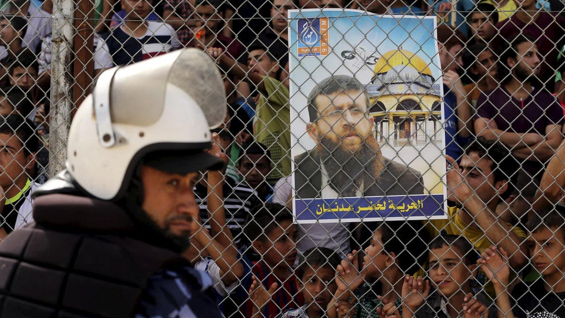 Palestinian policeman loyal to Hamas stands guard as spectators stand behind a fence and hold a poster depicting Palestinian prisoner Adnan. (Reuters)