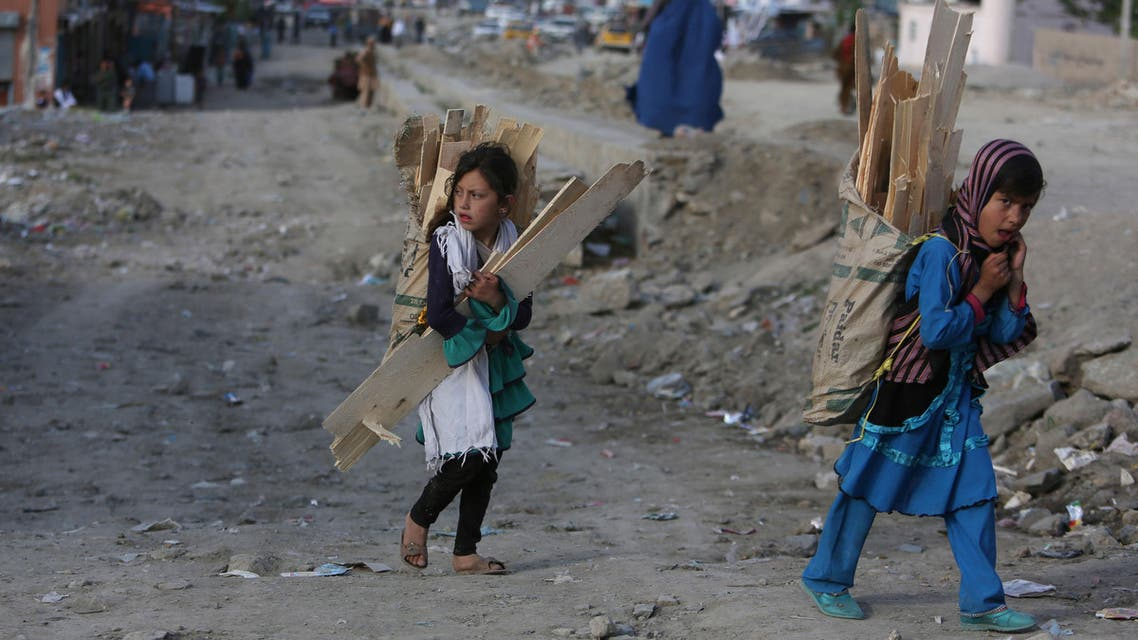 Afghan girls carry firewood on their back in Kabul, Afghanistan. Girls were far more likely to be kept away than boys. (File Photo:AP)