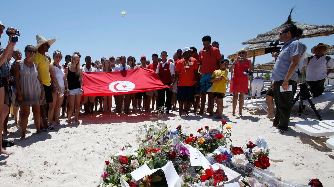 People, some displaying a Tunisian flag, stand in silence next to flowers during a gathering at the scene of the attack in Sousse, Tunisia, Sunday, June 28, 2015. AP