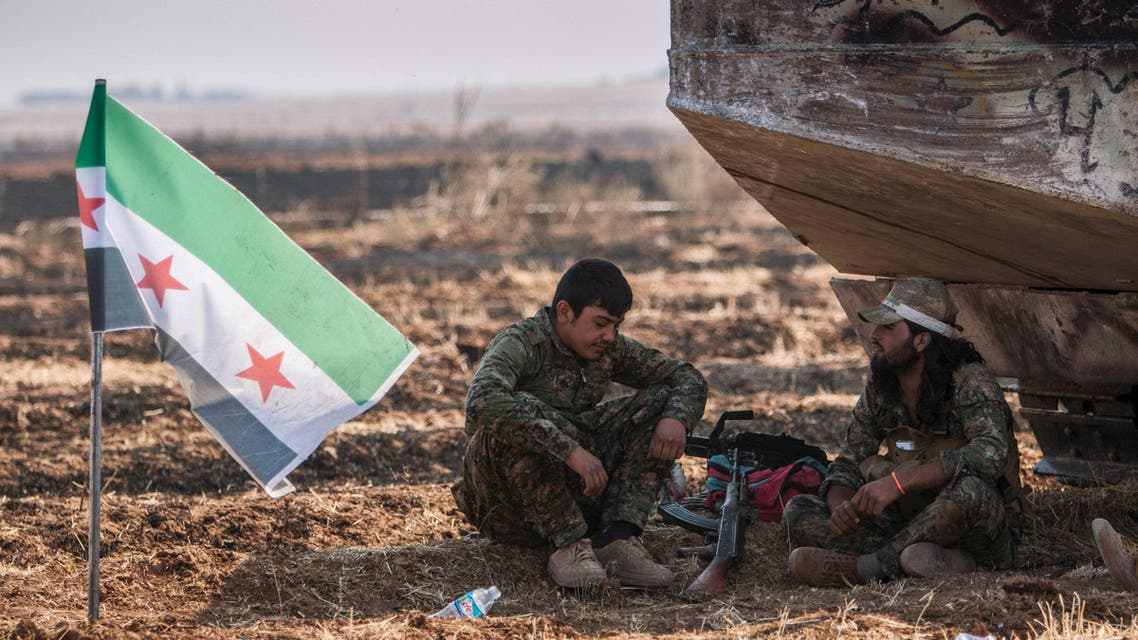 Fighters from the Free Syrian Army's Al-Tahrir Brigade, rest near their flag on the eastern outskirts of the city of Tel Abyad of Raqqa governorate after they said they took control of the area June 15, 2015. (Reuters)