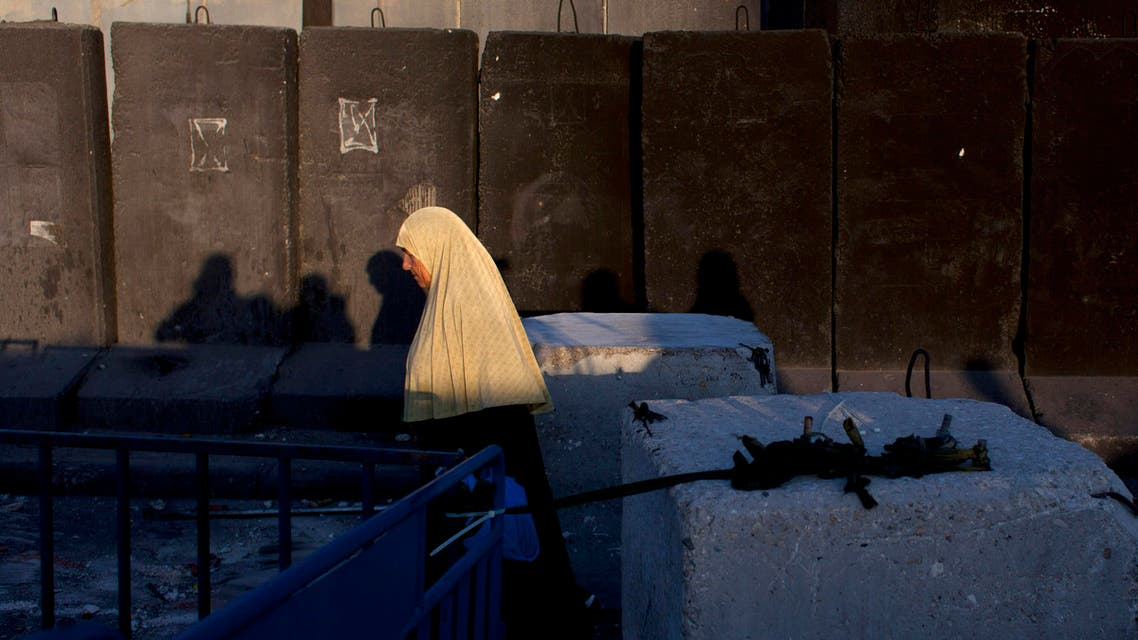 A Palestinian woman walks by the Israeli separation barrier on her way to Jerusalem through the Qalandia security checkpoint, on the outskirts of the West Bank city of Ramallah, Friday, July 4, 2014. (AP)