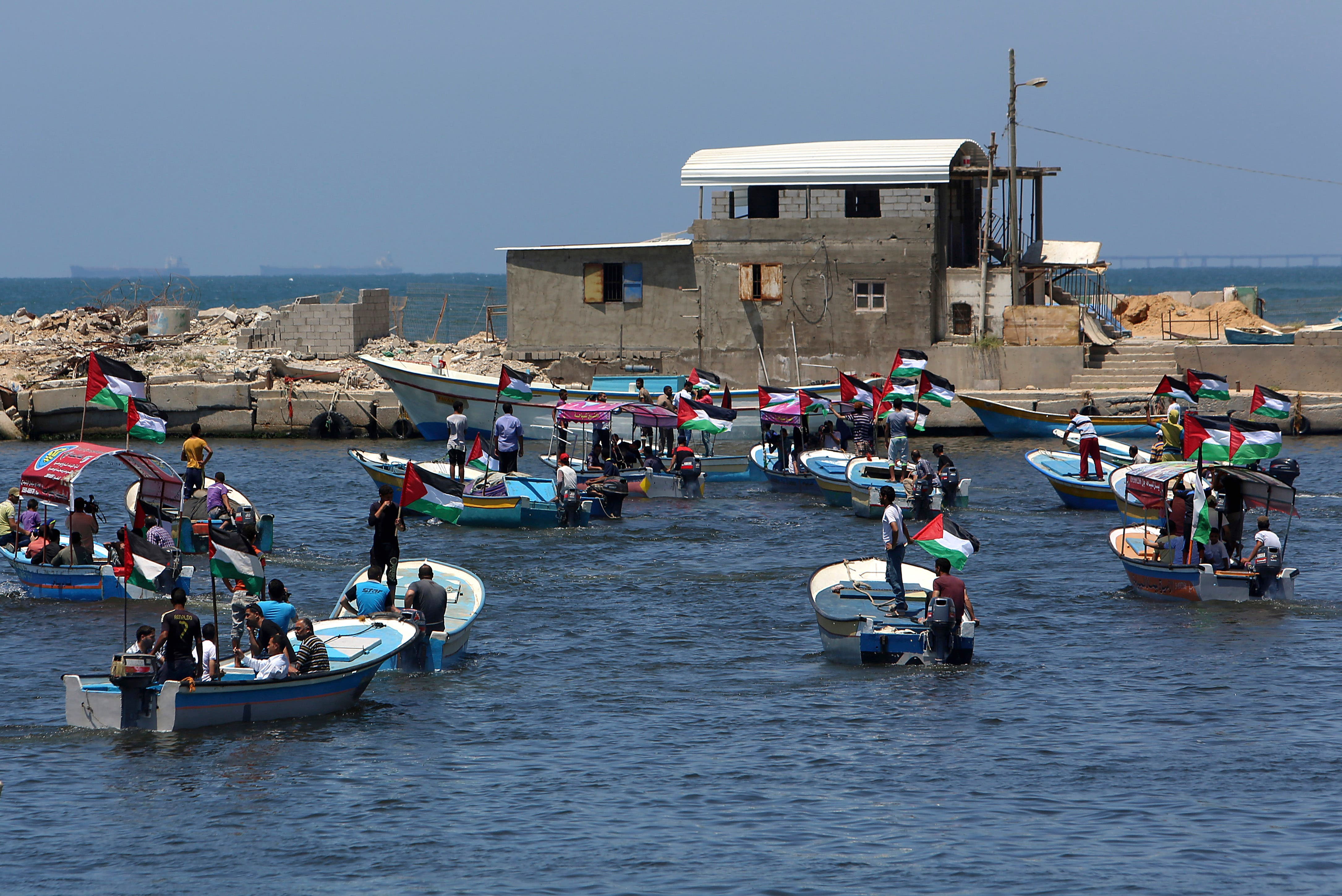 Palestinian protesters sail into the Mediterranean sea while waving their national flags during a protest calling to free the Marianne vessel one of four boats sailing to break the blockade on Gaza strip, at the fishermen port in Gaza City, in the northern Gaza Strip, Monday, June 29, 2015. (AP)