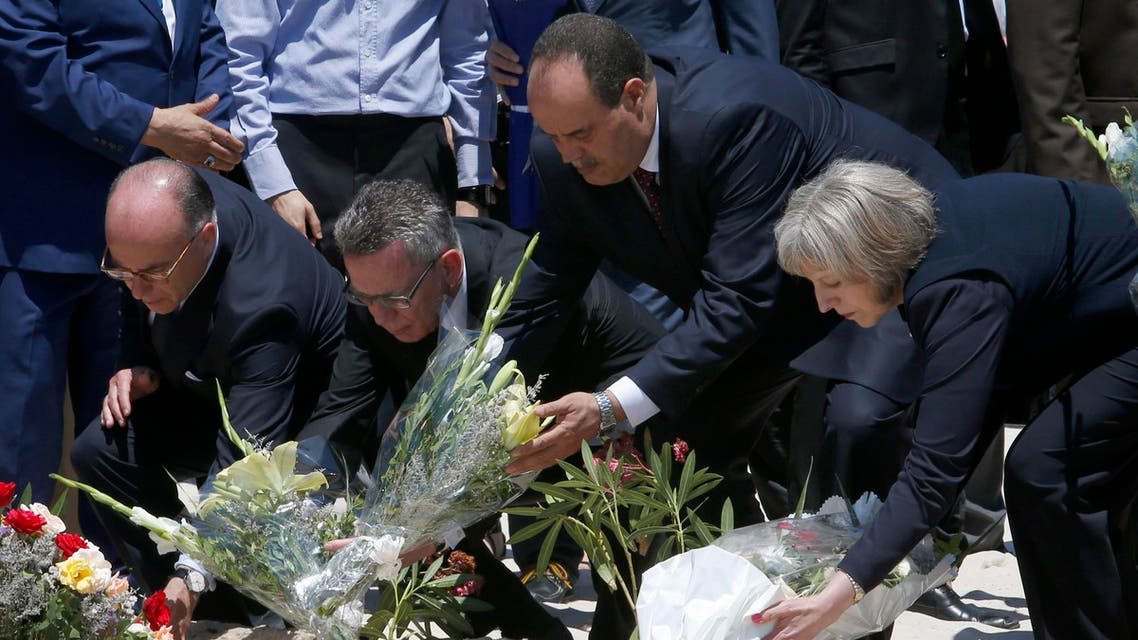 From right to left British Home Secretary Theresa May, Tunisian Interior Minister Mohamed Najem Gharsalli, , German Interior Minister Thomas de Maiziere and French Interior Minister Bernard Cazeneuve lay flowers on the beach in front of the Imperial Marhaba hotel in the Mediterranean resort of Sousse for the tribute in Sousse, Tunisa, Monday, June 29, 2015. AP