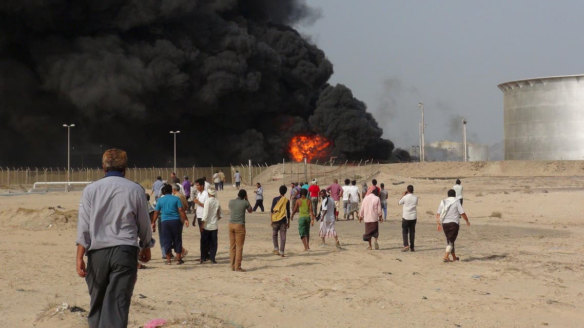 People gather at the site of a fire caused by missiles fired by Houthi fighters at storage tanks of the oil refinery in Yemen's southern port city of Aden June 27, 2015. (Reuters)