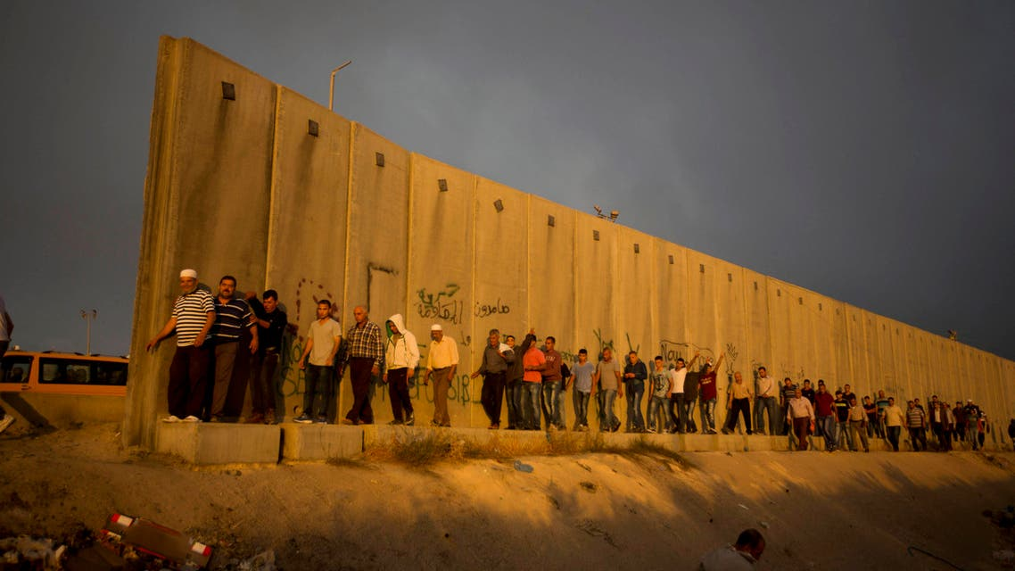 Palestinian men walk past a section of Israel's separation barrier to cross the Qalandia checkpoint on their way to pray at the Al-Aqsa Mosque in Jerusalem. (AP)