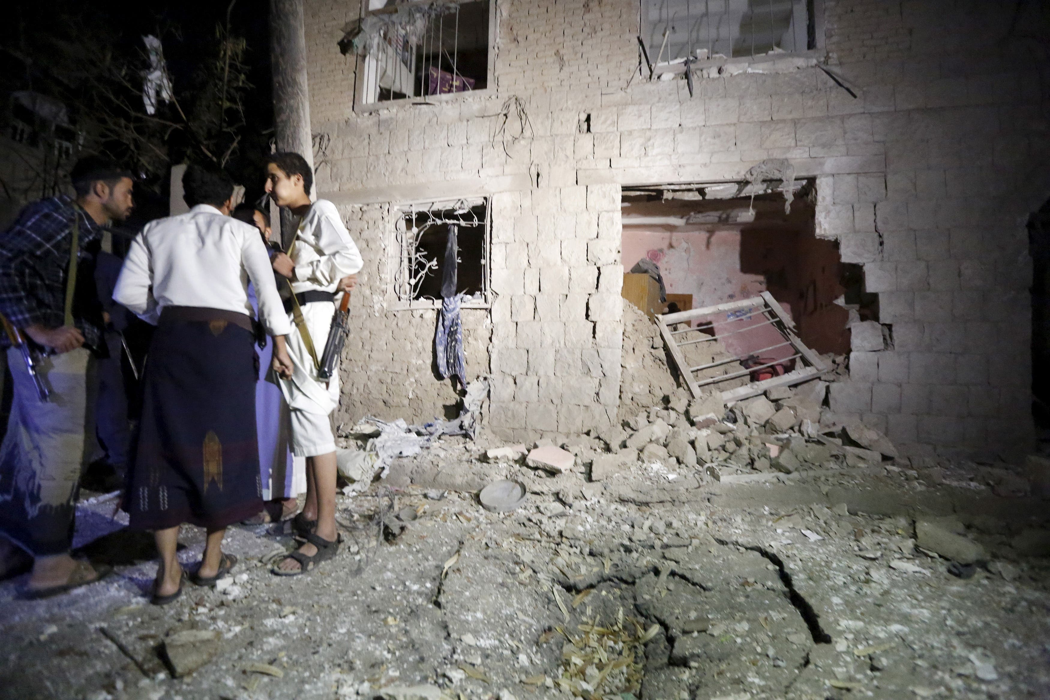 People stand next to a damaged house at the site of a car bomb attack in Yemen's capital Sanaa June 29, 2015.