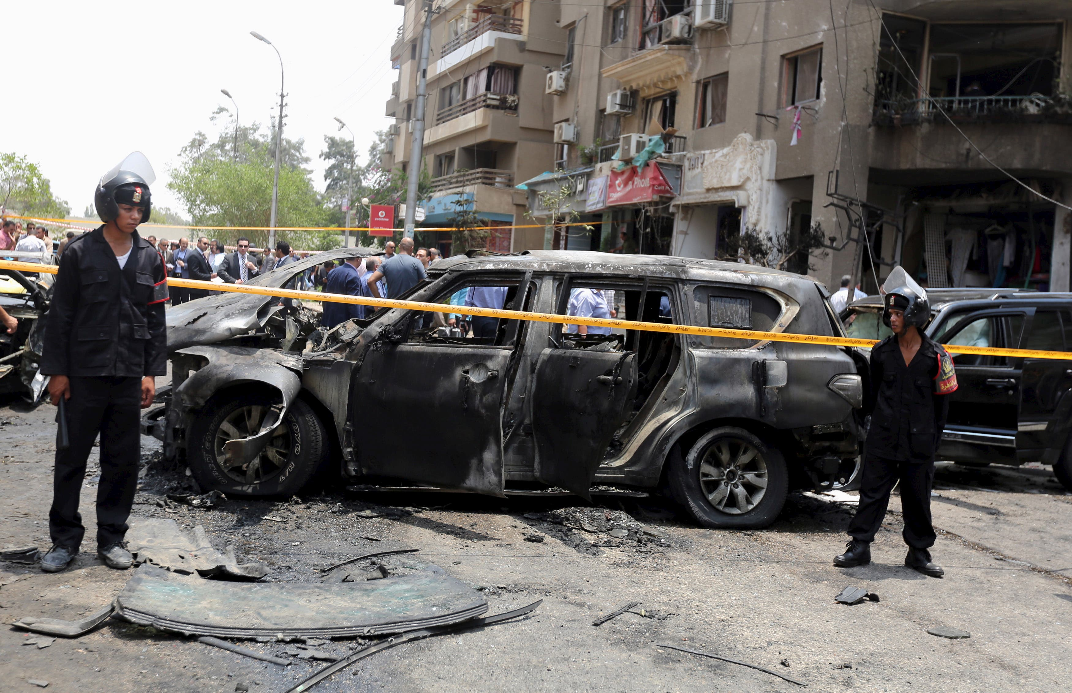 Policemen investigate the site of a car bomb attack on the convoy of Egyptian public prosecutor Hisham Barakat near his house at Heliopolis district in Cairo, Egypt, June 29, 2015.