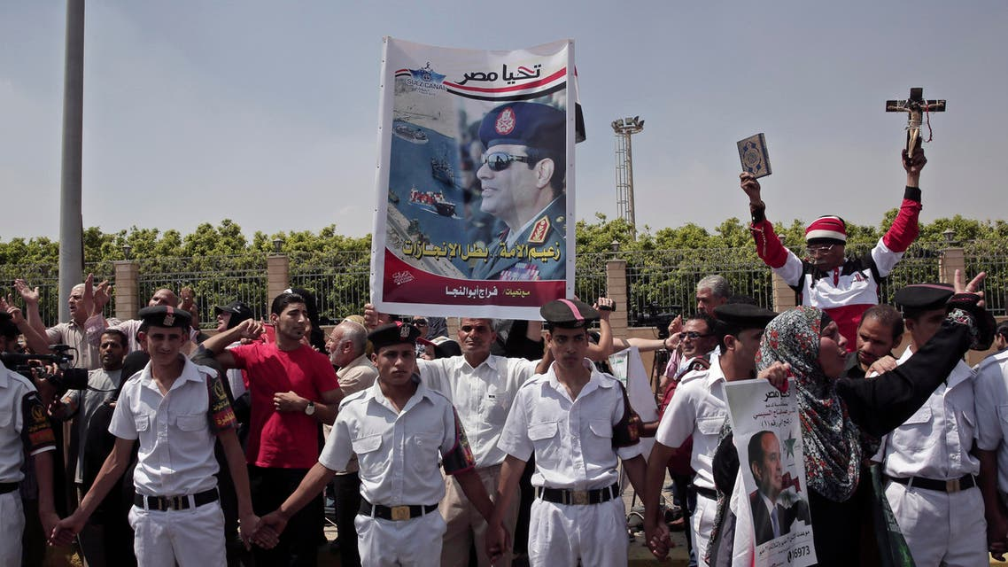 Security forces stand guard as mourners hold a poster of Egyptian President Abdel-Fattah el-Sissi, a cross and a Quran, during the funeral of Prosecutor General Hisham Barakat, killed in bomb attack a day earlier, outside the Hussein Tantawi Mosque in Cairo, Egypt, Tuesday, June 30, 2015. AP